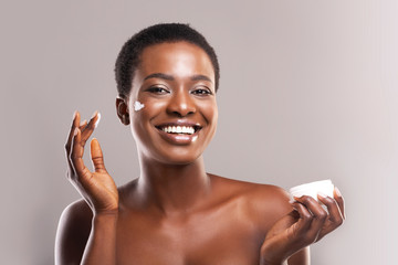 Fototapete - Happy Afro Woman Holding and Applying Moisturizing Cream on Face