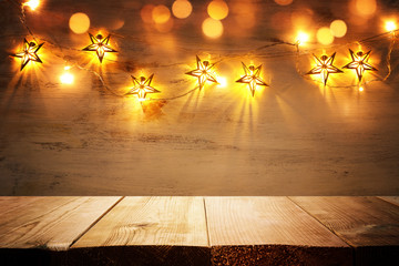 background image of wooden board table in front of Christmas warm gold garland lights. filtered. selective focus. glitter overlay