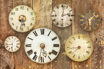 Vintage clocks hanging on an old weathered wooden wall