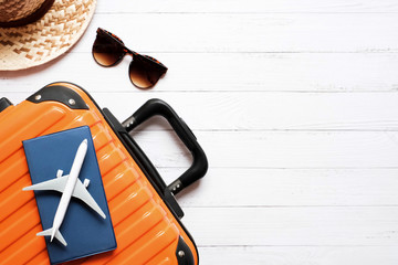 Flat lay planing and travel concept on white wooden table background with plane and passport on orange suitcase , hat and sunglasses, Top view with copy space