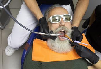 Bearded Senior man having dental treatment at dentist's office. Wall mural