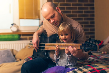 Cute little girl and her father are playing bass guitar and smiling while sitting on couch at home. Spending time together, learning to play the guitar