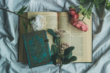 Open bible surrounded by decorative flowers and an intense blue notebook to write down