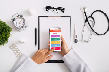 Doctor nutritionist using smartphone with opened daily diet plan application