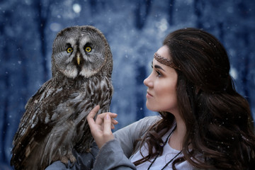 Fairytale image of a girl and an owl in the winter forest