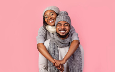 Happy african woman hugging her man from behind, winter set