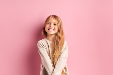 Portrait of positive cheerful girl cutely smiling at camera, girl with long golden hair in white...