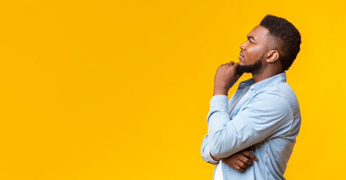 Young african american guy thinking about something over yellow background