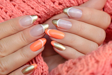 Colorful nail design with peach and golden nail polish. French manicure on a knitted orange background.