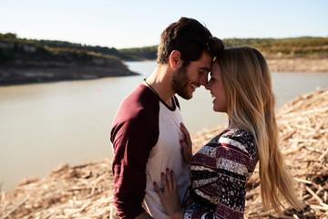 Loving couple hugging on river bank