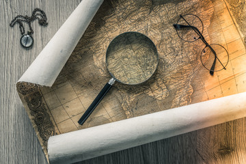 Old colonial map of South America with a magnifying glass, compass and period glasses.  Vintage style