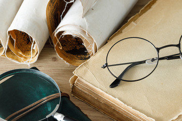 A book with old-fashioned glasses, a magnifying glass and rolled up old parchments