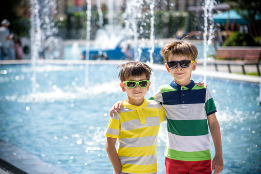 Group of happy children playing outdoors near pool or fountain. Kids embrace show thumb up in park during summer vacation. Dressed in colorful t-shirts and shorts with sunglasses.