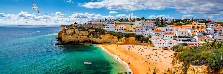 Poster Beach View of Carvoeiro fishing village with beautiful beach, Algarve, Portugal. View of beach in Carvoeiro town with colorful houses on coast of Portugal. The village Carvoeiro in the Algarve Portugal.