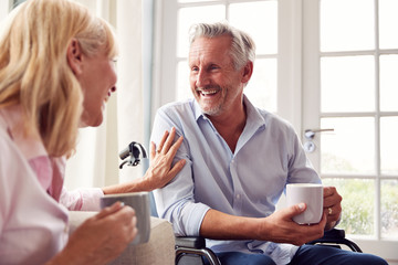 Mature Couple With Man In Wheelchair Sitting In Lounge At Home Talking Together