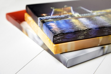 Photography canvas prints. Stack of colorful photos with gallery wrap on white wooden table. Stretched photo canvases, lateral side, closeup