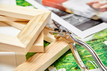 Canvas pliers and photography canvas prints. Tool for wrapping, colorful photos, pile of wooden stretcher bars