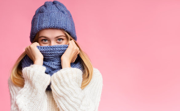 Enigmatic winter girl hiding from cold over pink background