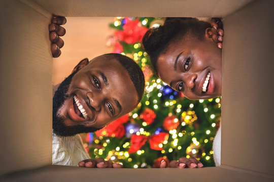 Excited afro couple opening Christmas present at home