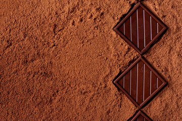 Chocolate bars lie in a row on cocoa powder, top view, free space for text. Fragrant black...