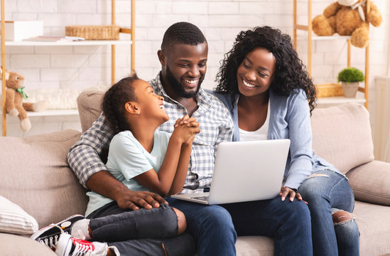 Happy african family watching movie on laptop at home together