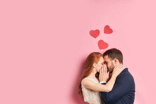 Portrait of beautiful couple kissing and hugging each other isolated over pink background.