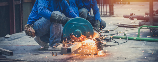 Close up view of professional focused two worker man in uniform working on the metal pipe