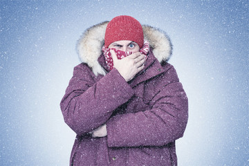 Frozen man in red winter clothes covers his face in the frost with his hand, cold, snow, blizzard