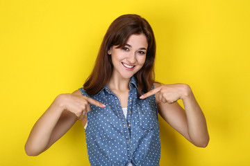 Young woman in stylish clothing on yellow background