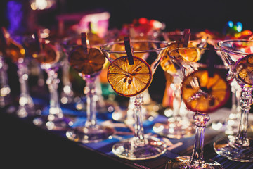 View of alcohol setting on catering banquet table, row line of different colored alcohol cocktails on a party, martini, vodka, and others on decorated catering bouquet table event