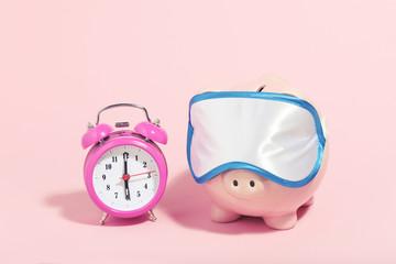 Piggybank with sleeping mask and alarm clock on pink background. Minimalism concept