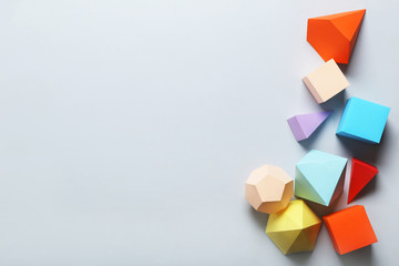 Colorful paper geometric figures on grey background