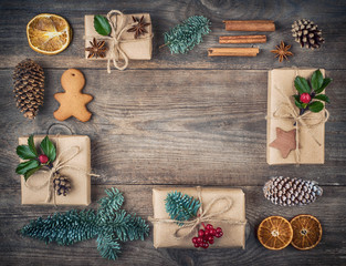 Christmas frame, background with decorations. Christmas gift, pine cones, fir branches, gingerbreads on wooden background.