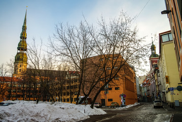 View to medieval houses in street of Riga old town and spire St.Peter's Church. Latvia. Winter morning.