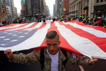 U.S. Army veteran Bradley Durfee carries the U.S. flag with members of Team Red, White & Blue during the Veterans Day Parade in Manhattan, New York City