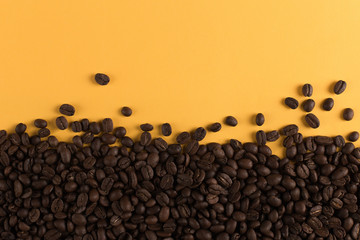 Coffee beans are scattered on a yellow paper background close-up, concept, commercial copy space.