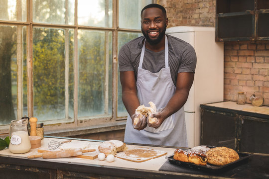 Baking process. Cheerful dark skinned African American male wears apron, kneads dough with great enthusiasm, being content to recieve praise from chef for endeavour and hard work in restaurant.