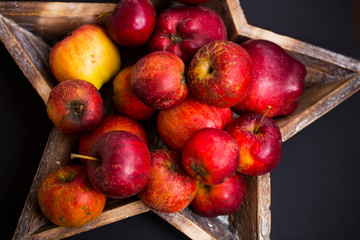 Red and yellow autumn apples in wooden tray, fresh tasty colorful seasonal fall apples fruits