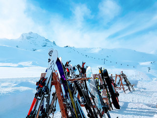Photo of multi-colored skis in snow at winter resort in afternoon.