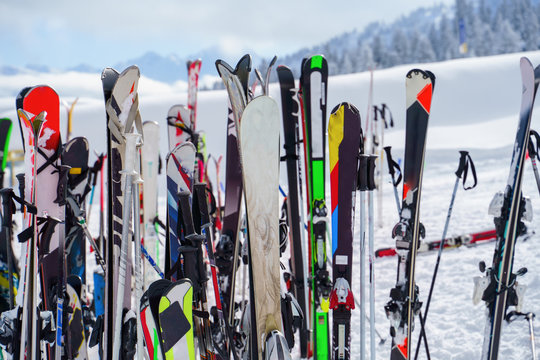 Image of multi-colored skis and snowboards in snow at winter resort in afternoon.