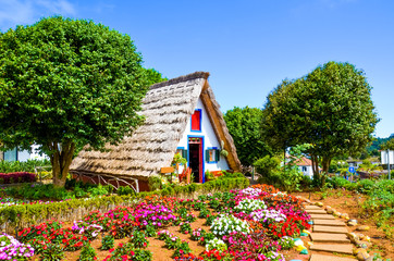 Amazing traditional houses in Santana, Madeira, Portugal. Wooden, triangular houses represent a part of Portuguese heritage. Front garden with beautiful colorful flowers. Tourist landmark Fototapete