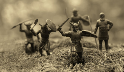 Five well armed attacking Vikings (toy soldiers), located on a mossy place, misty blurred background, selective focus, Old Norse Gods, Valhalla topic, epic myths, monochrome photo (sepia)
