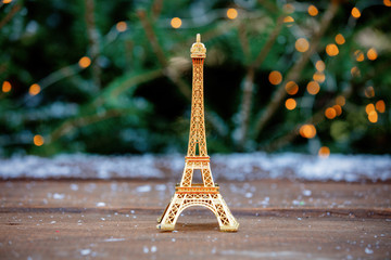 Fotobehang Eiffeltoren Golden eiffel tower souvenir on table with spruce on background