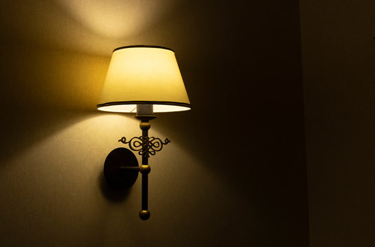 sconce lamp yellow electricity illumination in dark room interior silence and warm atmospheric environment wall background, empty copy space for your text