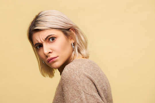Studio shot of blonde young woman turning head to camera frowning not being in mood to talk, feeling disturbed, having indignant facial expression, posing isolated, wearing beige warm sweater