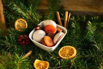 Schüssel mit Weihnachtsleckereien auf Tannenzweigen und Dekorationen im Sonnenlicht