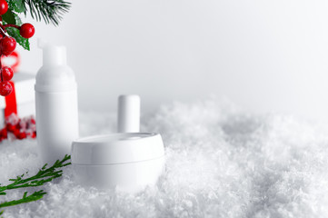 Skincare products bottles on snow covered surface. Blank containers with mistletoe and fir twigs backdrop. Christmas present for women idea. Winter season cosmetics banner with text space
