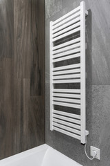White and modern heated towel rail in bathroom