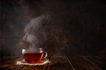 Foto auf Leinwand Tee Cup of hot tea with a steam on dark background