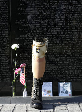 A prosthetic leg is placed next to a wall with names of fallen service members, at the Vietnam Veterans Memorial on the National Mall in Washington